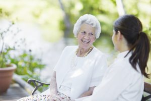 An elderly woman sitting alongside her caregiver on a bench in a garden